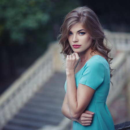 Outdoor lifestyle portrait of pretty young girl, wearing in blue dress on urban background. Stock fotó