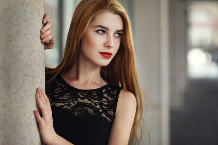 Outdoor lifestyle portrait of pretty young girl wearing in black dress on urban background.