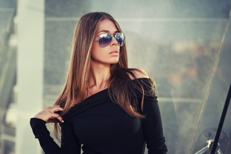 Beautiful brunette young woman in nice black dress, sunglasses. Fashion Photo