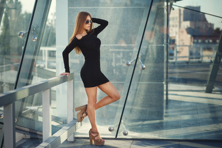 Beautiful brunette young woman in nice black dress, sunglasses, high heels sandals. Fashion Photo