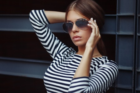 Beautiful brunette young woman in nice striped dress, sunglasses. Posing on urban background. Fashion Photo