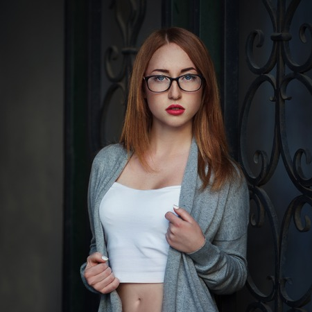 Beautiful redhair young woman in casual closes and glasses. Sitting on stairs. Fashion Photo