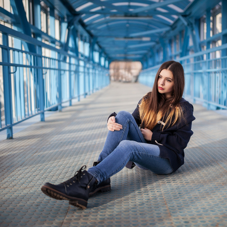 Outdoor fashion lifestyle portrait of pretty young girl, wearing in hipster swag grunge style urban background. Tomboy city concept