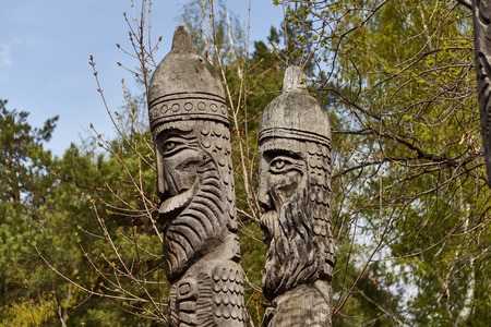 idols: Two sculptures of idols which are cut out from a tree stand against trees and the sky