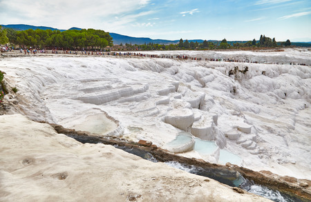 carbonates: The long chain of tourists walks on rocks in Pamukkale