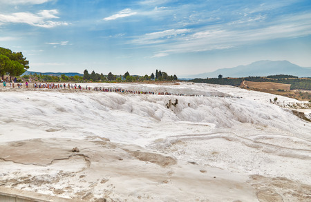 carbonates: The long crowd of tourists walks on rocks in Pamukkale