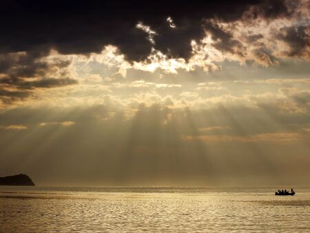 Sunrise over the sea and boat silhouette. The suns rays shine through the clouds radially