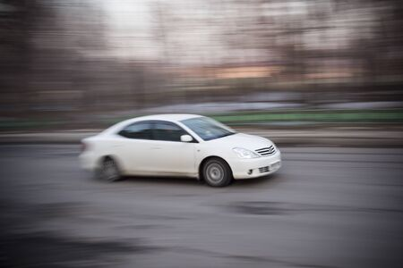 exceeds: Car motion. White car exceeds the speed in road the city.
