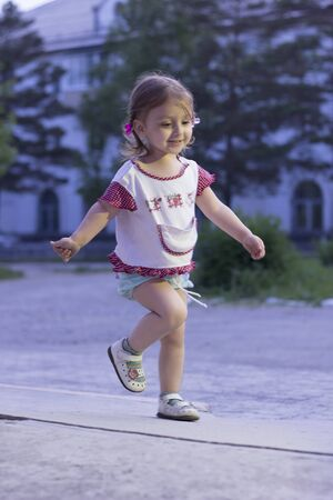 3 4 years: Little girl running. Happy girl 2-3-4 years old with braids running down the road in the park in the evening