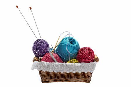 tejido de lana: Knitting yarn balls and needles in basket isolated on white background Foto de archivo