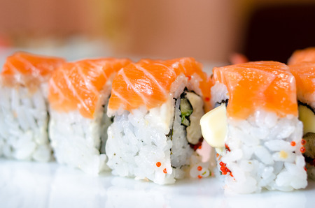 Rolls, sushi and ginger on a white plate and a light background. photo