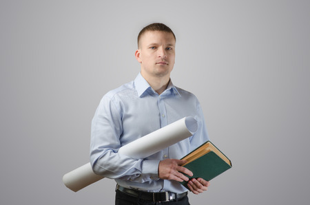 Serious young businessman holding blueprints and architect of the book. On a white background photo