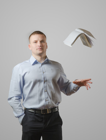 reluctance: A young man throws the book over his head. On a white background
