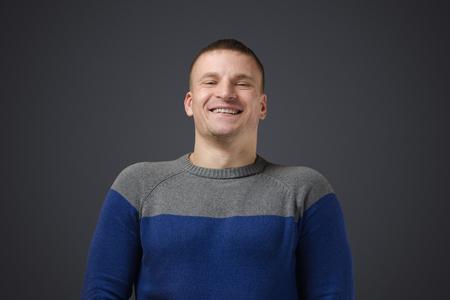 carita feliz: Retrato de un hombre joven gay que sonr�e. Foto emocional en el estudio sobre un fondo negro