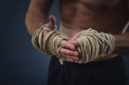 Close-up of a young Thai boxer hands hemp ropes are wrapped before the fight or training photo