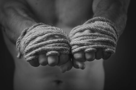 Hands Thai boxer in the foreground, the traditional hemp rope wrapped to match or training. Black and white style photo