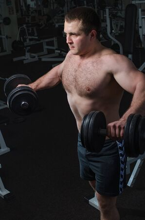 deltoid: Young man at the gym to exercise the deltoid muscle of the shoulder, lifting dumbbells to the sides