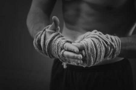 patada: Primer plano de un joven boxeador tailand�s manos cuerdas de c��amo se envuelven antes de la pelea o la formaci�n. Estilo blanco y negro