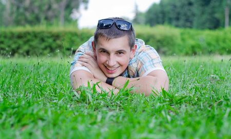 broadly: The young guy smiles broadly lying on a green lawn Stock Photo