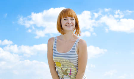 broadly: The young girl smiles against the blue sky broadly Stock Photo
