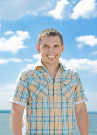 broadly: The young guy smiles against the blue sky broadly