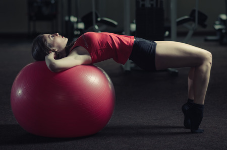 fitball: Young, beautiful, sports girl does exercises on a fitball at the gym. Toning. Stock Photo