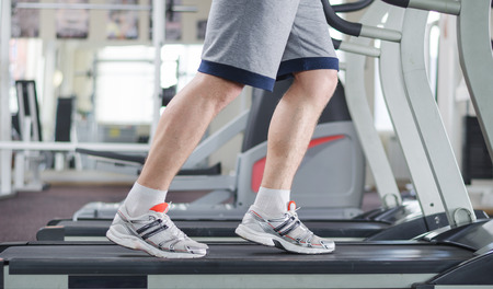 Muscular male legs on a treadmill at the gym
