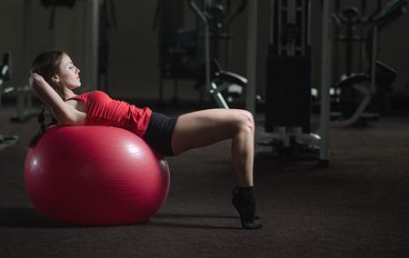 Jeune, belle, fille de sport fait des exercices sur une fitball au gymnase Banque d'images - 40504539