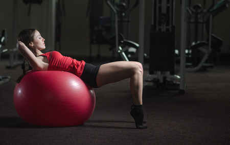 Young, beautiful, sports girl does exercises on a fitball at the gym 免版税图像