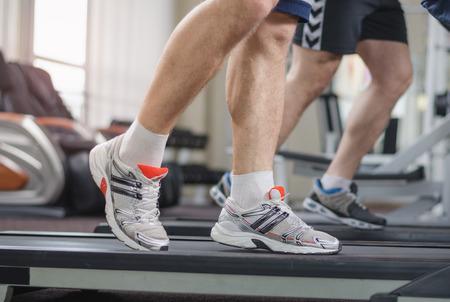 piernas hombre: Piernas masculinas musculares en una caminadora en el gimnasio