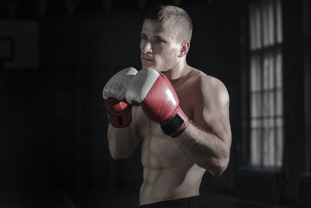 Young athletic man with boxing gloves and a rack