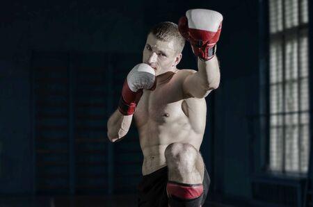 patada: Hombre atlético joven con guantes de boxeo y un estante