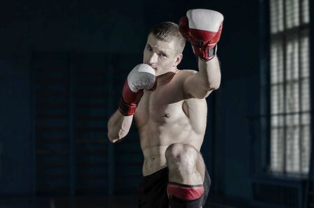 kick boxing: Young athletic man with boxing gloves and a rack