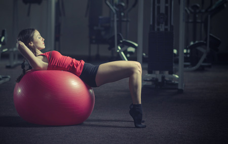 stability: Young, beautiful, sports girl does exercises on a fitball at the gym. Toning. Stock Photo