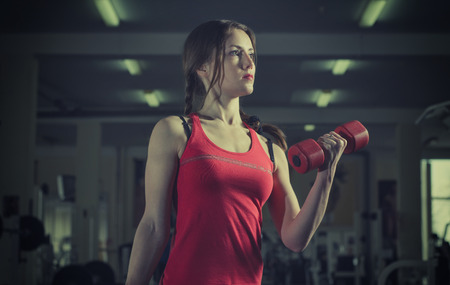 toning: Young, beautiful, sports girl does exercises with dumbbells in the hands of the gym. Toning.