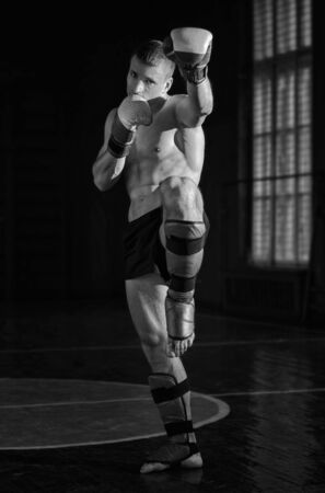 thai kick boxing: Young athletic man with boxing gloves and a rack. Black and white photo