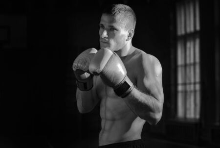 combative sport: Young athletic man with boxing gloves and a rack. Black and white photo