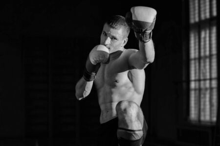 thai arts: Young athletic man with boxing gloves and a rack. Black and white photo