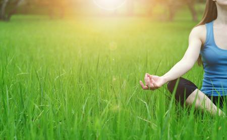 Primo piano di una mano di una giovane ragazza che pratica yoga in natura. Lotus postura. Soleggiato highlight cade a portata di mano. tonificante caldo.