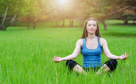 Young girl practicing yoga in nature in the woods on a background of green trees and grass.Woman covers a ray of sunshine at sunset