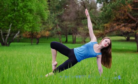 meditating woman: Young girl practicing yoga in nature in the woods on a background of green trees and grass. Stock Photo