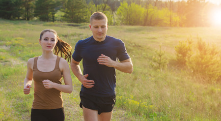 solar flare: Young couple running at sunset outdoors. Solar flare illuminates a couple back.Hands in motion blur