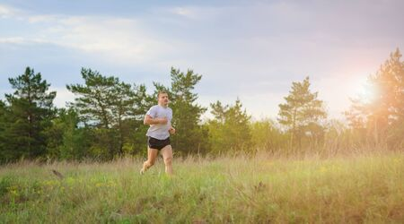 flare up: Young man jogging outdoors. The man is running up the hill. Solar flare from sunset
