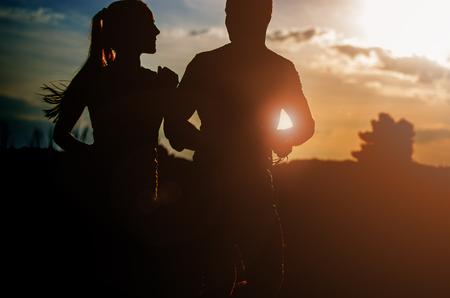 야외에서 일몰을 실행하는 젊은 부부. 태양 플레어는 한 쌍의 등불을 비 춥니 다. 스톡 콘텐츠
