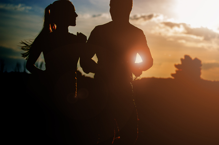 man and woman silhouette: Young couple running at sunset outdoors. Solar flare illuminates a couple back.