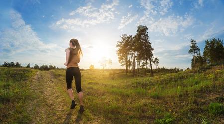 야외에서 조깅 젊은 여자. 햇빛과 녹색 필드의 패치로 푸른 하늘의 배경에 뒷면에서 볼 수 있습니다.