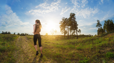 Young woman jogging outdoors. View from the back, on a background of blue sky with patches of sunlight and green field. Standard-Bild