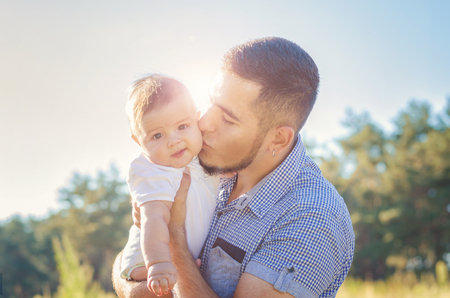 solar flare: Young daddy kissing a baby. Walk autumn evening outdoors. Solar flare illuminates the baby and dad.
