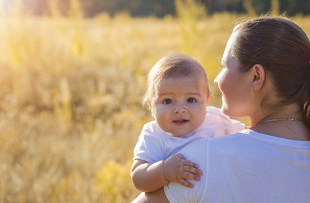 solar flare: Young beautiful mother holding a baby in her arms. Walk in the autumn warm evening outdoors at sunset. Solar flare lights Woman and child. Stock Photo