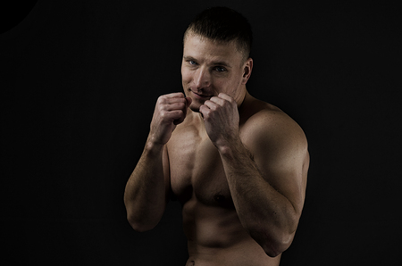 model male: Young muscular man with boxing defensive stance against a black background. Hard light, dark lighting Stock Photo